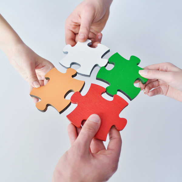 A team of business people fitting puzzle pieces together